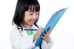 Smiling Asian Chinese Little Doctor Writting On Clip Board Stock Photos