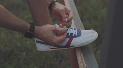 Man runner tying shoelace in the nature Stock Footage