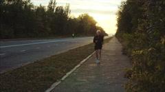 Senior gray haired man jogging on sunset city street Stock Footage