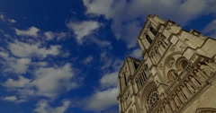 Camera movement of the facade of the Notre Dame cathedral with clouds and blue Stock Footage