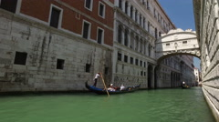 A gondola is rowed by a gondolier in Canal Grande. Stock Footage