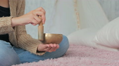 Young woman in cardigan relaxing with nepal singing bowl Stock Footage