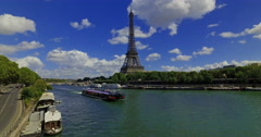 A cruise boat pass next to the Eiffel tower on a sunny day in Paris, France. Stock Footage