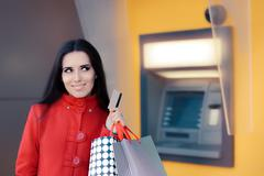 Happy Shopping Woman Holding Credit Card in front of an ATM Stock Photos