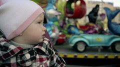 Slow Motion close-up of a little Girl looking at Carousel in amusement Park Stock Footage