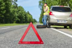 Man in reflective vest calling to a car assistance after breakdo Stock Photos