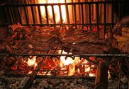 Cooking the meat on the grill in the big fireplace in the restaurant Stock Photos