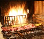 Hot fire in the fireplace in the restaurant with lots of pork and beef meat Stock Photos