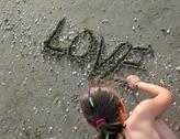 Little girl writes the word LOVE on beach in summer Stock Photos