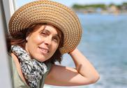 Beautiful real lady forty years old without makeup with straw hat on the ship Stock Photos
