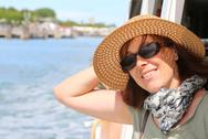 Smiling beautiful woman with straw hat and sun glasses on the ship while trav Stock Photos