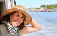Smiling beautiful woman with straw hat while cruising in the sea Stock Photos