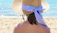 Young girl with straw hat beside the beautiful sea in summer Stock Photos