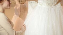 Young redhead woman choosing wedding dress in bridal boutique. bride preparing Stock Footage