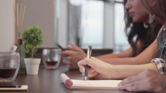 Asian girls writting on note pad in cafe setting  Stock Footage
