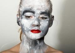 Abstract art makeup. Face and neck girls smeared with gray colors and bright red Stock Photos