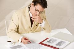 Thinking businessman reading the document Stock Photos