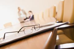 Glasses with pen over document on the background of businesspeople Stock Photos