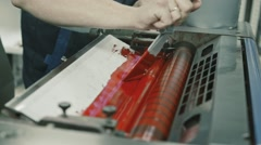 Worker at Polygraphy printing industry use Red paint on ink roller, close up Stock Footage