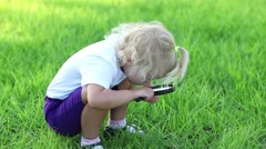Little girl sitting on the grass and looks through a magnifying glass. Stock Footage