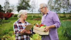 Senior couple with box of vegetables on farm Stock Footage