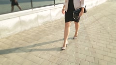Pretty girl walking in high heels down the street in the sun Stock Footage