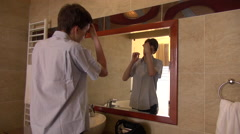 Young man looking in a mirror and fixing his hair  Stock Footage