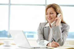 Female chief speaking by telephone and writing something while looking at laptop Stock Photos