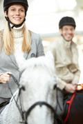 A young woman learning to ride a horse against a man Stock Photos