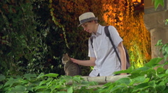 Teenager petting a stray cat in a beautiful romantic garden Stock Footage