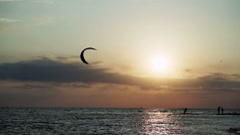 Kitesurfing. Kitesurfers going surfing on the surfboards on waves at sunset. HD Stock Footage