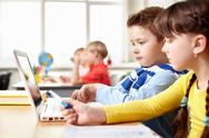 Two little children sitting at table in school and looking at laptop screen Stock Photos