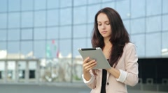 Pretty girl using tablet computer on the street Stock Footage