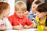 A little boy sitting at table and drawing and his friends looking at him Stock Photos