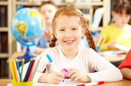 Portrait of a little red haired schoolgirl sitting in classroom, looking at came Stock Photos