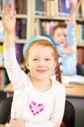 Portrait of a little schoolgirl raising her hand to answer Stock Photos