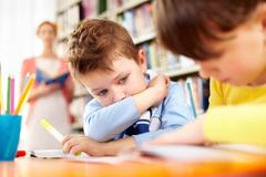 A little schoolboy sitting at table and looking at his working classmate Stock Photos