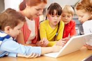 A teacher and her four students working with computer Stock Photos