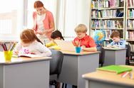 Little school kids busy with their schoolwork and a teacher looking after them Stock Photos