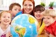 A happy teacher and her little students looking at camera behind the globe and s Stock Photos