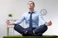 A businessman meditating on grassy table Stock Photos
