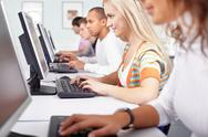 Selective focus of a girl working with computer among other students Stock Photos