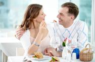 A young girl sitting with her boyfriend in cafe and feeding him with a fork Stock Photos