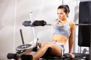 A young girl training on exercise machine in gym Stock Photos