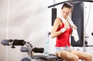 A young girl sitting on exercise machine with a towel Stock Photos