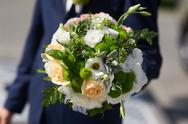 Groom holding a beautiful wedding bouquet of roses Stock Photos