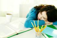 Young teenage girl falling asleep while doing homework Stock Photos
