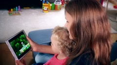 Nanny woman with little child girl watch family movie on tablet computer screen Stock Footage
