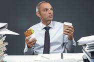 Manager with sandwich and coffee at his workplace Stock Photos