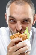 Hungry office worker chewing sandwich Stock Photos
